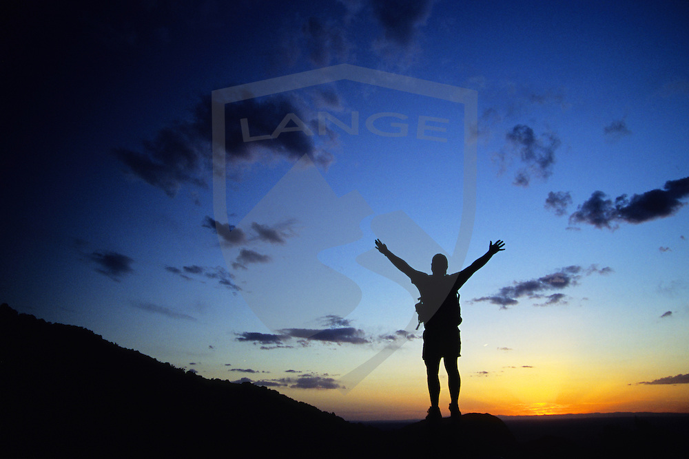 nature scenery and inspiring people: happy man silhouetted against sunset sky with his arms raised high, sandia mountains, albuquerque, new mexico, horizontal, copy space, wide angle