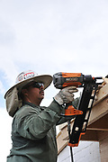 Thunder's rumbling in the background, so it's time to finish the roofing carpentry job. This Crest Construction crew member is putting the finishing touches on the drip edge trim installation.