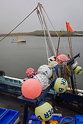 Fishing buoys are attached to the rear of a boat moored in a Northumbrian North Sea town harbour, on 25th September 2017, in Amble, Northumberland, England.