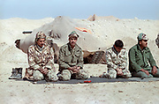 Egyptian soldiers perform afternoon prayers along the sand berm border wall separating Kuwait from Saudi Arabia February 8, 1991 in Ar Ruqi, Saudi Arabia. Egyptian soldiers are part of the coalition of nations in Operation Desert Storm to liberate Kuwait from Iraqi occupation.