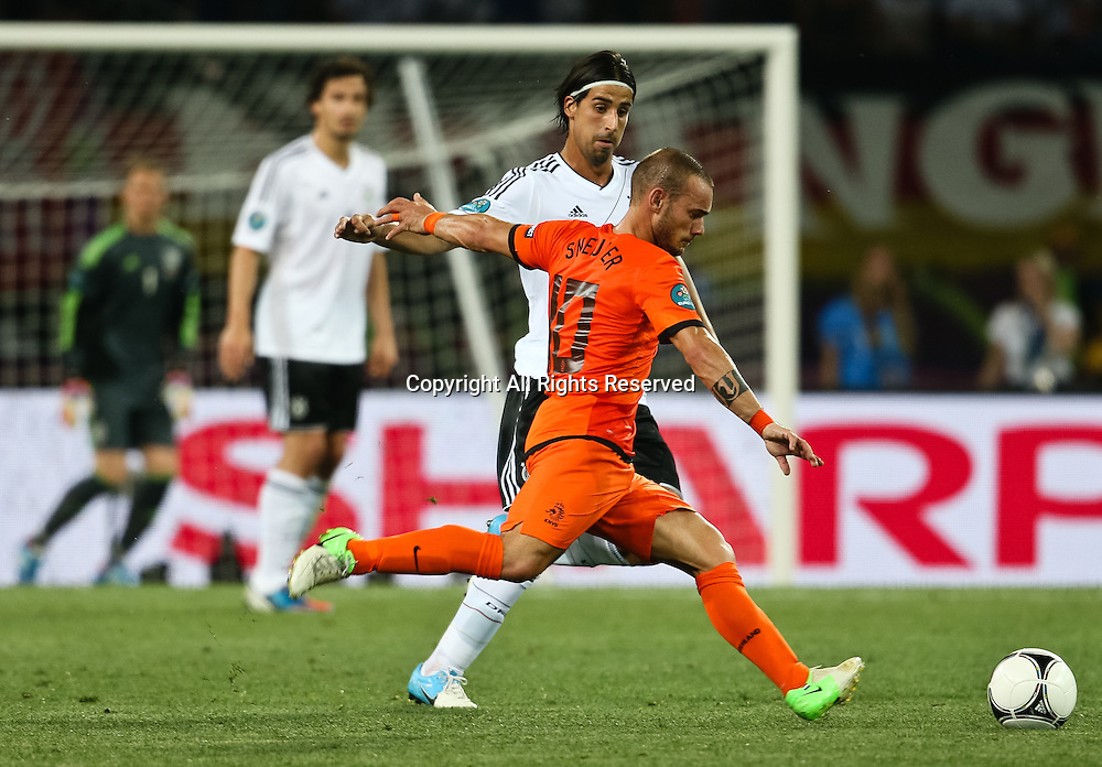 13.06.2012 Ukraine, Kharkiv.  Netherlands national team player Wesley Sneijder (in front) and German national team player Sami Khedira (back) in the group stage European Football Championship match between teams of the Netherlands and Germany.