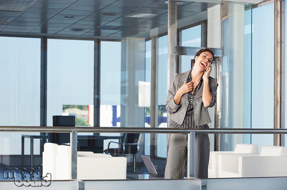 Businesswoman standing in office talking on mobile phone