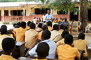 Calvin Doe stands in front of the Mbaem community school and tells the students about the new demonstration garden that will soon be coming to their community. Calvin is the volunteer Youth Ambassador for The Kraft Cocoa Partnership.