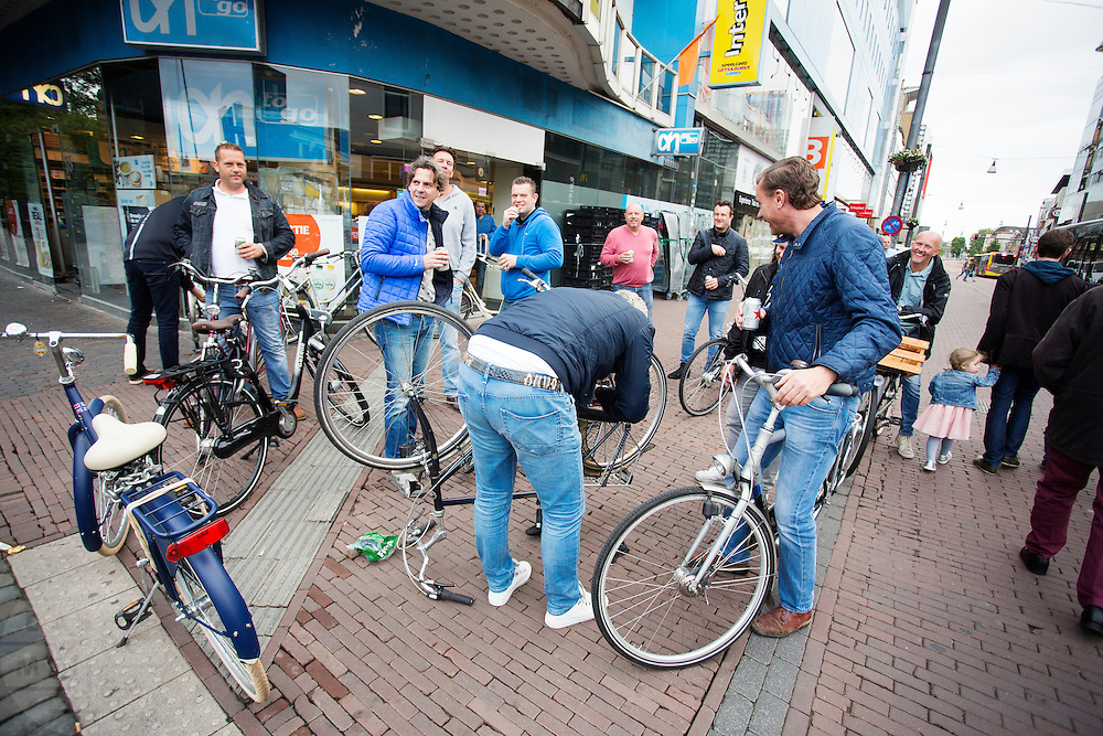 In Utrecht kijkt een groep vrienden lachend toe hoe een van hun zijn fiets repareert omdat de ketting eraf ligt.<br /> <br /> In Utrecht a group of friends watch one of them fixing his bicycle.