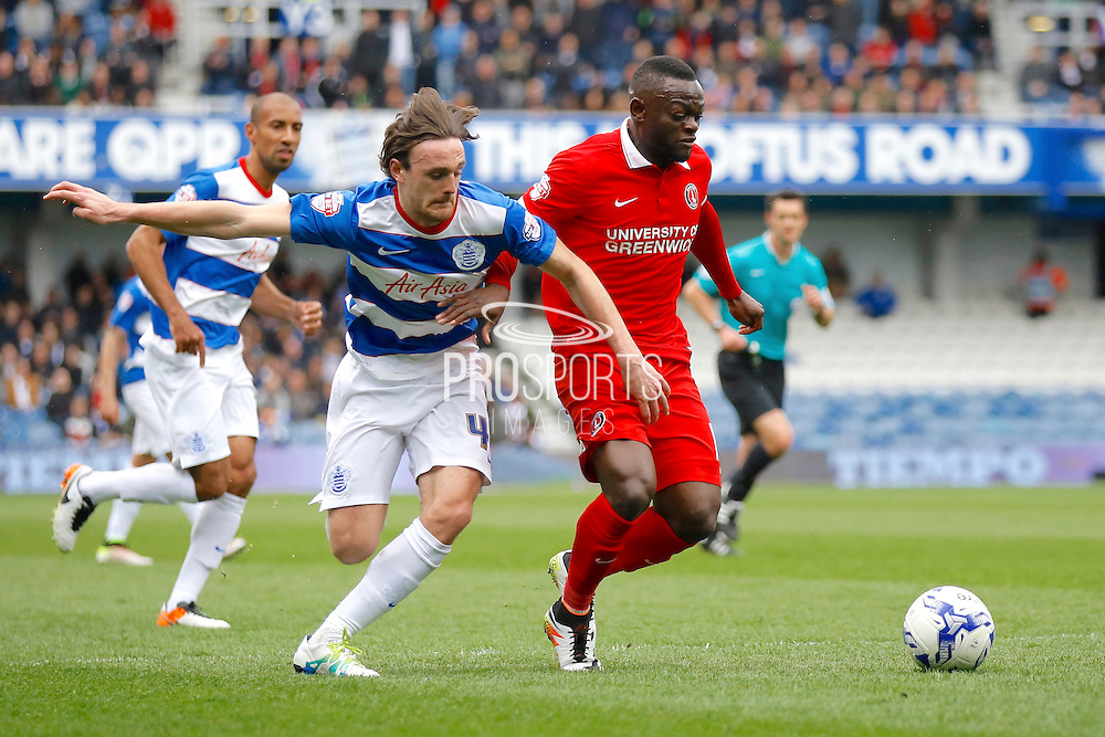 Charlton Athletic striker Igor Vetokele (14) muscles passed Queens Park Rangers defender Jack Robinson during the Sky Bet Championship match between Queens Park Rangers and Charlton Athletic at the Loftus Road Stadium, London, England on 9 April 2016. Photo by Andy Walter.
