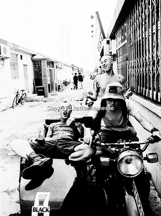 "BEIJING, HAIDIAN DISTRICT,CHINA-AUGUST15,1999:.a group of punks hang out together in the alley outside the Scream Club before a punk show, August 15, 1999, in China.. In the spring of 1998, a handful of youngsters teamed up to unofficially rebel against conformist Chinese life. They shaved their heads, and founded bands with names like ""Brain Failure"" and ""Anarchy Boys"".  To some like Punker Xiao Rong, this lifestyle was an extension of the life he'd begun as a school dropout at age sixteen.-Although the majority of the punks came from well-off families, they preferred to live in self-imposed poverty. .The Scream Bar and its surrounding dusty alleyways in the student district became the center of youthful rebellion until it was closed . The punks bands have moved on to other bars in Beijing, some got contracts with foreign record companies and even toured Europe, Japan and the US."
