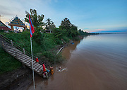 Laos, Champasak province. Vat Phou Cruise. Staying overnight next to a Buddhist temple at northern tip of Don Khong.  Buddhist monks taking a sunset bath in the Mekong.