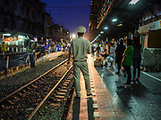 13 MAY 2015 - BANGKOK, THAILAND: A station master is silhoutted by a train coming into Wong Wian Yai train station in the Thonburi section of Bangkok. Wong Wian Yai is the Bangkok terminus of the Mahachai Short Line, a commuter train that runs to the fishing port of Mahachai in Samut Sakhon province.     PHOTO BY JACK KURTZ