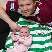 Arbroath defender Mark Baxter pictured with his 2 week old daughter Eva. Mark almost missed the Celtic v Arbroath Scottish Cup game at parkhead due to the birth of his daughter..   Eva is pictured laying on Beram Kayal's shirt that Mark got on the evening as a momento.<br /> Picture by Graeme Hart.<br /> Copyright Perthshire Picture Agency<br /> Tel: 01738 623350  Mobile: 07990 594431