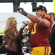 During ESPN Samantha Pounder's presentation of the Offensive MVP award to Trojan Center and Punahou Graduate, Abe Markowitz, USC teammates began chanting &quot;Four more years&quot; to the 6th year player.  Markowitz responded to them with the &quot;Fight On&quot; victory sign and smiles.  The USC Trojans defeated the Fresno State Bulldogs 45-20 at the Royal Purple Las Vegas Bowl, Sam Boyd Stadium, Las Vegas, Nevada.  Photo by Barry Markowitz, <br /> 12/21/13, 5pm