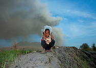A child under a Volcanic Eruption In Tavurvur Volcano, Rabaul, New Britain Island, Papua New Guinea. Some people still live in the volcano area as they do not have enough money to leave their homes. All day long,<br />