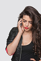 Thoughtful young woman using cell phone over gray background