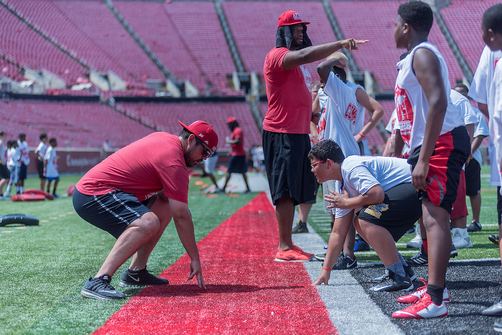 Former University of Louisville football players Mike Donoghue and George Bussey help students with their defensive line posture during the American Football Without Barriers youth football camp at Papa John's Cardinal Stadium. June 25, 2016 June 25, 2016
