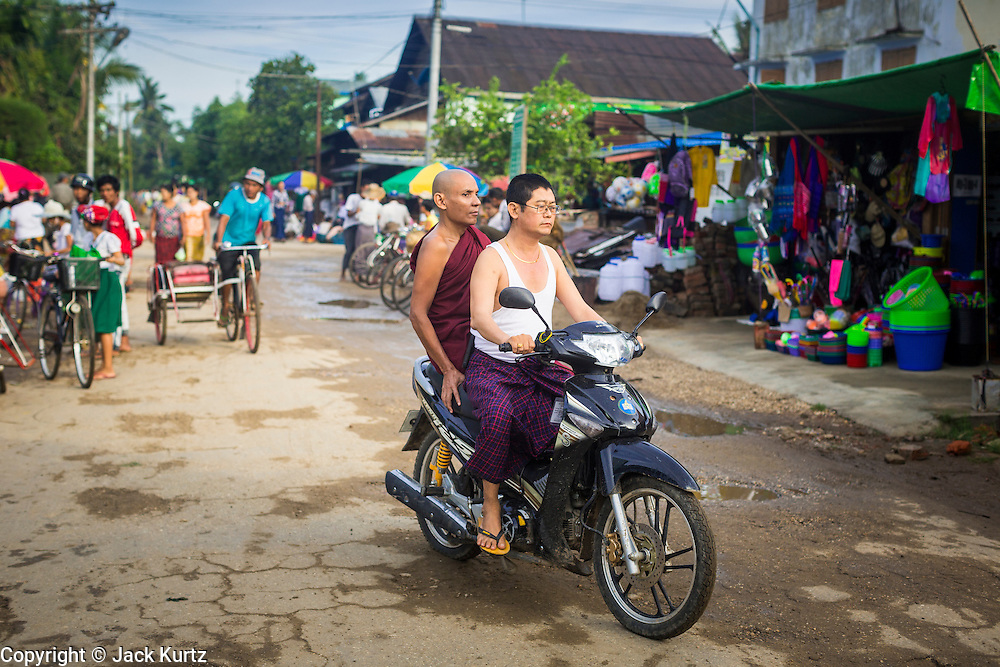 06 JUNE 2014 - IRRAWADDY DELTA,  AYEYARWADY REGION, MYANMAR: A man brings a Buddhist monk into Pantanaw on a motorcycle. Pantanaw is a town in the Irrawaddy Delta (or Ayeyarwady Delta) in Myanmar. The region is Myanmar's largest rice producer, so its infrastructure of road transportation has been greatly developed during the 1990s and 2000s. Two thirds of the total arable land is under rice cultivation with a yield of about 2,000-2,500 kg per hectare. FIshing and aquaculture are also important economically. Because of the number of rivers and canals that crisscross the Delta, steamship service is widely available.   PHOTO BY JACK KURTZ