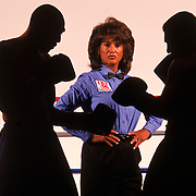Gwen Adair, pro boxing's only  female referee, poses between two silhouetted boxers in a Los Angeles boxing club.