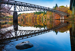 Spectacular late autumn tree colours and bridge is  reflected in the waters of Loch Faskally in Pitlochry, Perthshire, Scotland, UK.