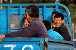 China, Beijing, Chaoyang, San Jian Fang, 2008. Demolition workers head home in a blue diesel flatbed truck. Hundreds of businesses have been summarily evicted to make way for the widening of Chaoyang Street east of the city center..