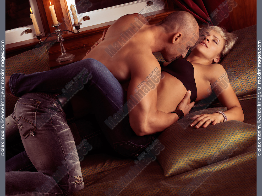 Young muscular man and a woman making love in bed