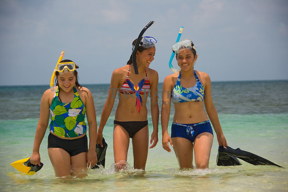 Three young women snorkeling and playing,  South Water Caye, Belize