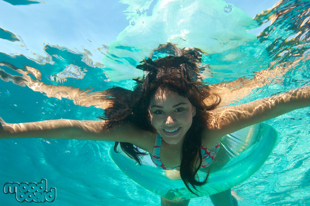 Young woman swimming in pool, underwater view