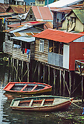 Fishermen's traditional wood houses (palafitos) rise on stilts in Castro on Chiloé Island, in Los Lagos Region, Zona Austral, Chile, South America. Colorful boats are moored on the sea water below. Founded in 1576, Castro is the capital of Chiloé Province. Isla de Chiloé is the largest island in Chile.