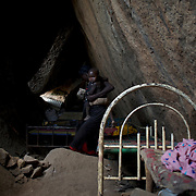 April 28, 2012 - Tabania, Nuba Mountains, South Kordofan, Sudan: A Nuba family takes cover, from possible bombardments by Sudan's Army Forces airplane, in some caves near Buram village. Since the 6th of June 2011, the Sudan's Army Forces (SAF) initiated, under direct orders from President Bashir, an attack campaign against civil areas throughout the South Kordofan's province. Hundreds have been killed and many more injured...Local residents, of Nuba origin, have since lived in fear and the majority moved from their homes to caves in the nearby mountains. Others chose to find refuge in South Sudan, driven by the lack of food cause by the agriculture production halt due to the constant bombardments of rural areas.