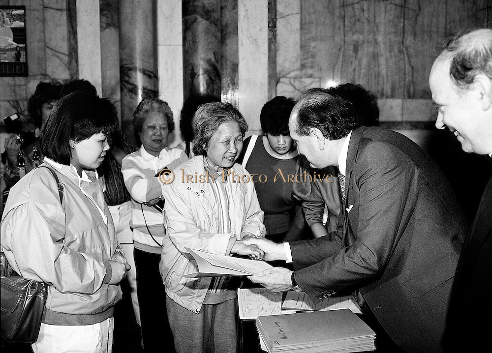 Justice Minister Gerard Collins TD presents a large group of Vietnamese refugees with certificates of naturalisation at the Department of Foreign Affairs in Iveagh House. The group of 156 adults, dispossessed due to the Vietnam war, arrived in Ireland from Vietnam and some refugee camps in Hong Kong and Malaysia.<br /> 8 July 1987