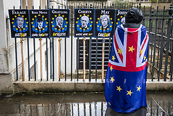© Licensed to London News Pictures. 02/04/2019. London, UK. An anti-Brexit protester opposite Parliament as rain falls over London. Prime Minister Theresa May is chairing a Cabinet meeting to try and agree a path forward with ministers after MPs voted to reject all alternatives to the Withdrawal Agreement for a second time. Photo credit: Rob Pinney/LNP