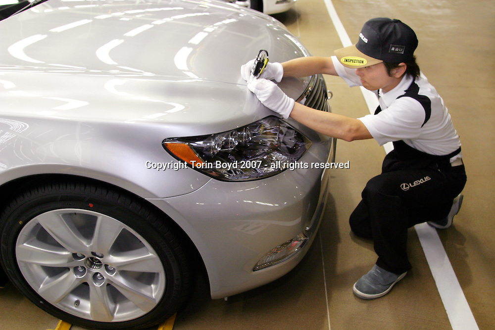 This is the inspection section of the Lexus assembly line of Toyota Motor Corp's Tahara plant located in Aichi Prefecture. This view shows a worker conducting a special inspection on a Lexus hybrid for blemishes on 36 spots using a hand held digital measuring device that takes 15 to 20 minutes for each car. At this plant Toyota manufactures the Lexus models: LS600h (hybrid launched in Japan in May 2007), the 600hl, LS460, 460L, GS450h, 430, 350, 300, IS350 and 250. On average there are 670 vehicles manufactured here every day, which is about one car every 83 seconds coming off the line. Also unique to this plant is the rigid quality control standards that checks for scratches, imperfections, and noise levels in the cab.