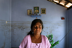 A woman, whose family lost nine members in the tsunami, is seen in their destroyed home in the village of Dutch Bar, Batticaloa, Sri Lanka, Jan. 15, 2005. The walls still show the height of the water level when the tsunami struck their town. Residents of the small Christian village spent more than six weeks in a makeshift refugee camp at the local convent recovering from the devastating tsunami that hit the eastern and southern borders of Sri Lanka. They were then moved into another temporary living camp, while awaiting the building of new homes.