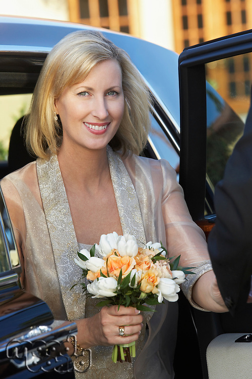 Middle-aged woman holding bouquet in open door of limousine, portrait