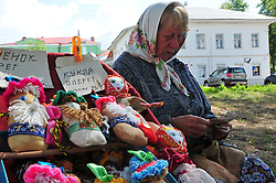 "A vendor sells handmade dolls for children on a walkway near the Volga River in Uglich, Russia. As one of Russia's ""Golden Ring"" cities, Uglich is designated a town of significant cultural importance."