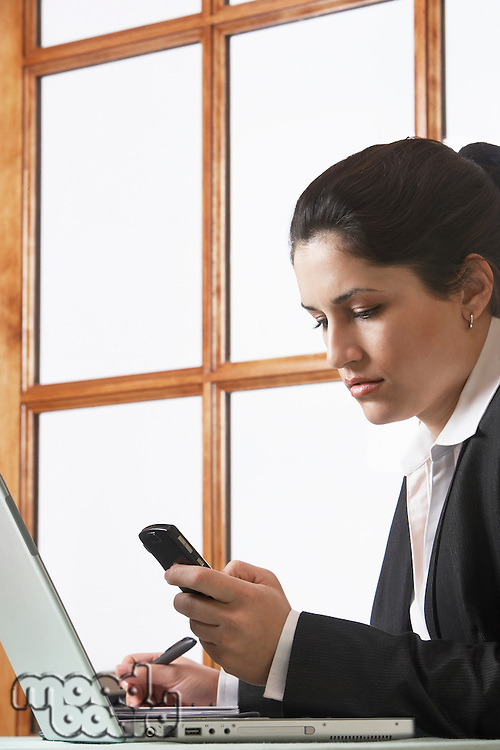 Business woman text messaging using mobile phone in office