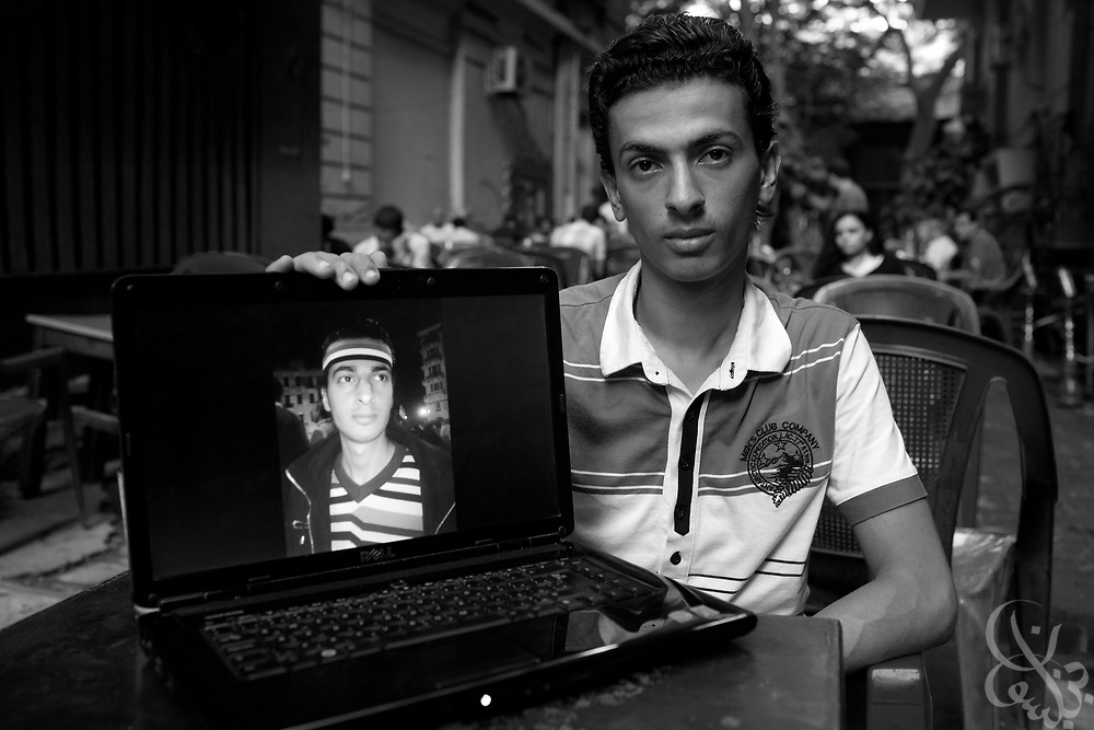 Mark Nabil, age 18, sits for a portrait  in a street cafe in dowtown Cairo, Egypt July 30, 2011. Nabil's brother Maikeal, (seen in image on laptop) age 24 was the first blogger arrested and put through a military trial after the revolution for insulting the military. (Photo by Scott Nelson for Stern)