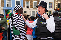 "London, August 24th 2014. A police officer and an ""escaped convict"" share a joke as thousands of Londoners of all races and cultures attend Notting Hill Carnival's ""Family friendly"" day ahead of the main carnival on August Bank Holiday Monday."