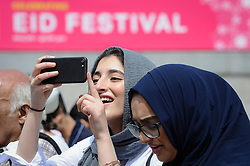© Licensed to London News Pictures. 23/06/2018. LONDON, UK.  A woman takes a photo during the EID Festival in Trafalgar Square, an event hosted by The Mayor of London.  The Mayor's festival takes place in the square one week after the end of Ramadan and includes a variety of stage performances and cultural activities.  Photo credit: Stephen Chung/LNP