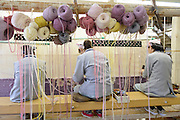 Three workers sit at a loom hand weaving a carpet together. Oriental Carpet Mills, Yamanobe-machi, Yamagata, Japan, April 11, 2016. Oriental Carpet Mills was founded in 1935 and produces luxury hand-woven and tufted carpets. Its carpets are used all over the world, including in the Vatican, the Imperial Palace in Tokyo and the Kabukiza Kabuki Theatre.