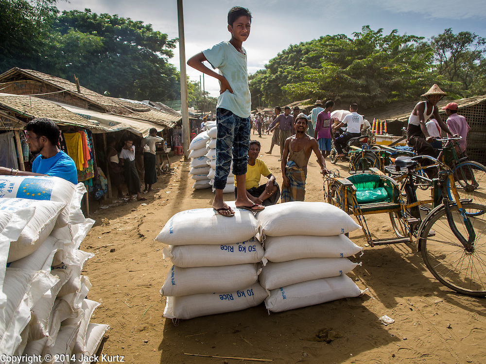 06 NOVEMBER 2014 - SITTWE, RAKHINE, MYANMAR: A Rohingya stands on 50 kilo (102 pounds) sacks of rice in a ration distribution center in a Rohingya Muslim IDP camp near Sittwe. After sectarian violence devastated Rohingya communities and left hundreds of Rohingya dead in 2012, the government of Myanmar forced more than 140,000 Rohingya Muslims who used to live in and around Sittwe, Myanmar, into squalid Internal Displaced Persons camps. The camps are about 20 minutes from Sittwe but the Rohingya who live in the camps are not allowed to leave without government permission. The government says the Rohingya are not Burmese citizens, that they are illegal immigrants from Bangladesh. The Bangladesh government says the Rohingya are Burmese and the Rohingya insist that they have lived in Burma for generations. They are not allowed to work outside the camps, they are not allowed to go to Sittwe to use the hospital, go to school or do business. The camps have no electricity. Water is delivered through community wells. There are small schools funded by NOGs in the camps and a few private clinics but medical care is costly and not reliable.   PHOTO BY JACK KURTZ