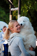 A blond young woman kissing and hugging her samoyed dog