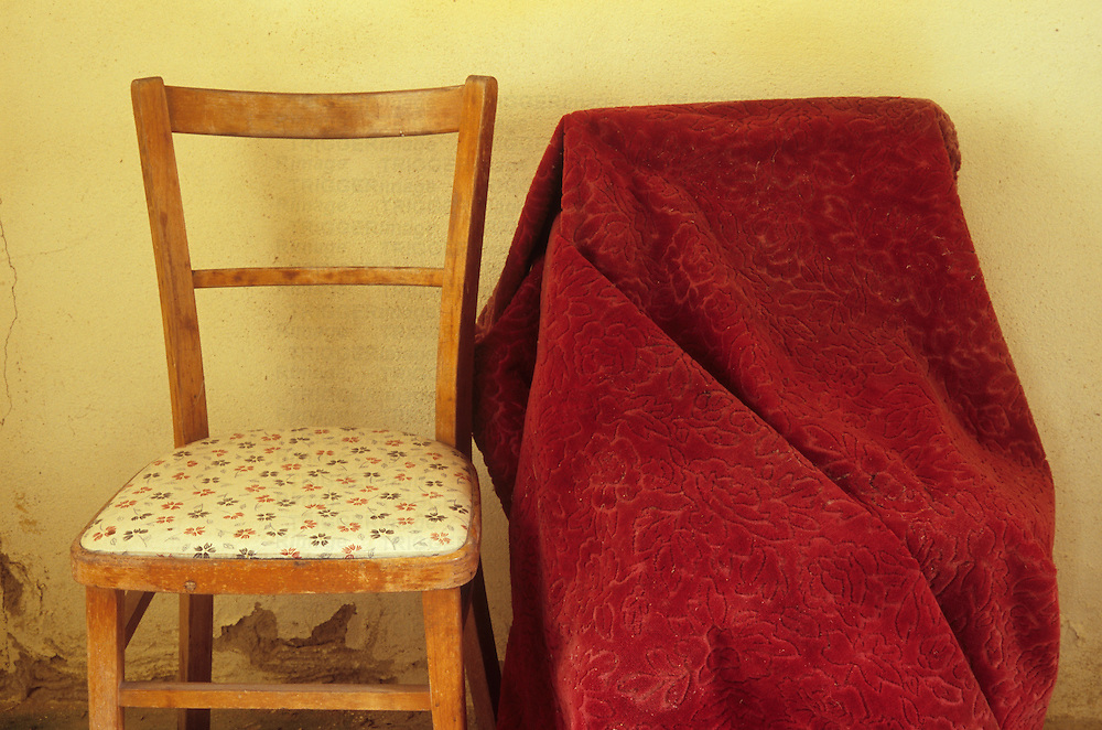 Basic wooden upright kitchen chair with seat covered with plastic with flower motif standing next to large object shrouded in red velvet
