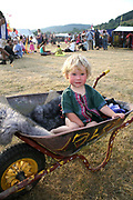 Young Girl in a wheelbarrow at the Workhouse Festival, Wales, 2006