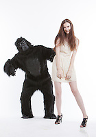 Portrait of smiling young woman with man in gorilla costume against white background