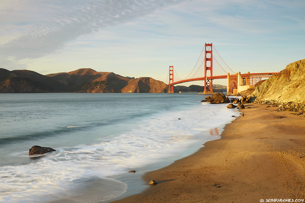 Scenic view of Golden Gate Bridge at sunset with a person walking down Marshall's Beach far off in the background. San Francisco, California, USA