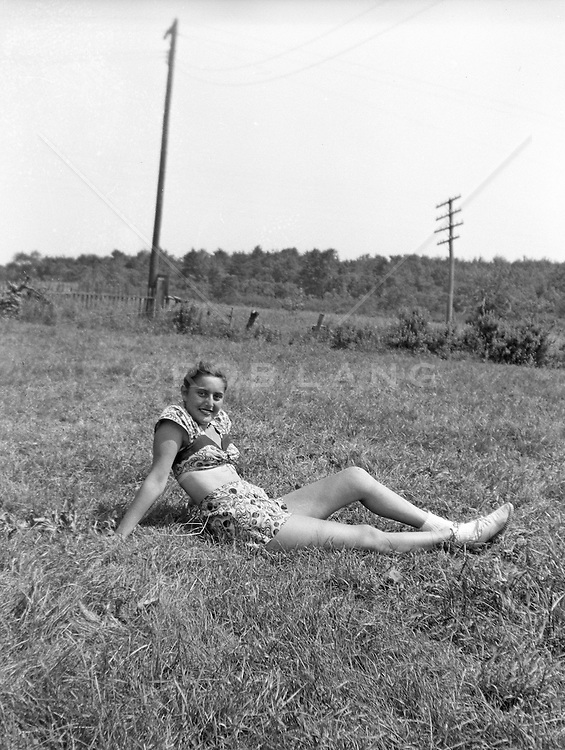 Woman relaxing on a lawn in a two peice bathing suit