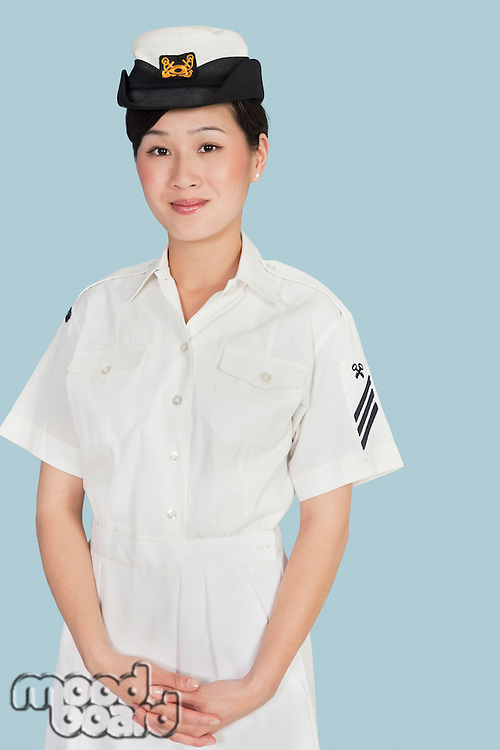 Portrait of a young female US Navy officer standing with hands clasped over light blue background