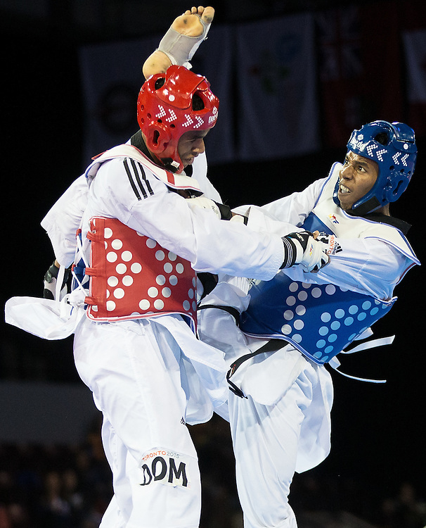 Jose Cobas (R) of Cuba lands a kick to the head of Moises Hernandez of the Dominican Republic during their gold medal contest in men's taekwondo -80 kg division at the 2015 Pan American Games in Toronto, Canada, July 21,  2015.  AFP PHOTO/GEOFF ROBINS