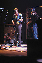 Phil Lesh performing with the Grateful Dead in Concert at the Brendan Bryne Arena on April 1st 1988. Side view from stage left. Bob Weir with back to the camera adjusting gear.