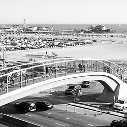 Santa Monica Beach pedestrian bridge and pier with Pacific Coast Highway in black and white. Panorama photo is 1:3 ratio. Copyright ⓒ 2017 Paul Velgos with All Rights Reserved.