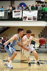20 February 2016:  Joel Pennington(12) works this way past Kyle Wuest during an NCAA men's division 3 CCIW basketball game between the Elmhurst Bluejays and the Illinois Wesleyan Titans in Shirk Center, Bloomington IL