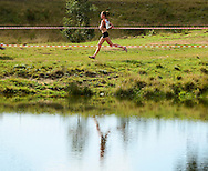 GEORGE, SOUTH AFRICA - SEPTEMBER 10: Nicole van der Merwe of Central Gauteng Athletics (CGA) runs past the small dam in the junior women 8km during the  2016 South African Cross Country Championships held at The Olympia School of Skills in Pacaltsdorp on September 10, 2016 in George, South Africa. (Photo by Roger Sedres/Gallo Images)